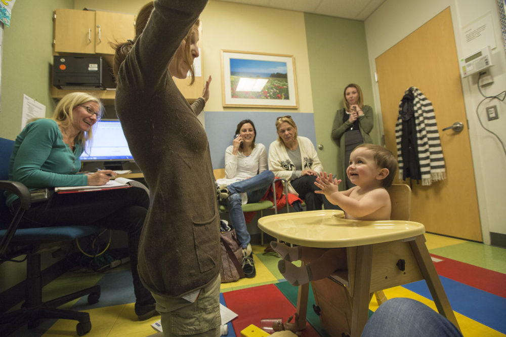 James smiles and claps as occupational therapist Victoria Peake tests his development  during a check up at the Newborn Developmental Follow up Clinic at Massachusetts General Hospital. Director of the Clinic, Dr. Leslie Kerzner is seated left and James' adoptive mother Kristen Fountaine in the center. (Jesse Costa/WBUR)