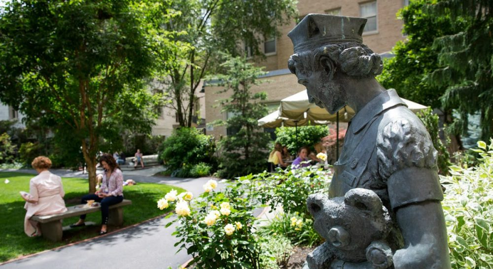 A statue of a nurse holding a bear near the entrance to Prouty Garden from Boston Children's Hospital's main building. More than 15,000 people have signed a petition to save the garden from demolition. (Robin Lubbock/WBUR)