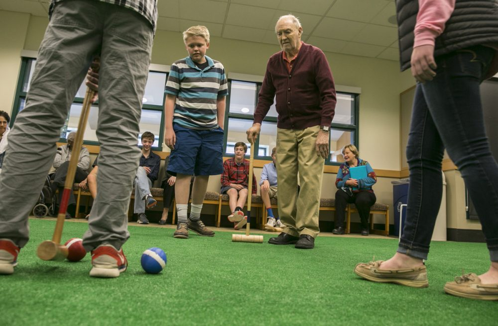 Greg Kintzele, left, and Bill Taylor, right, watch as others play croquet at Graland Country Day School in Denver. (Nathaniel Minor/CPR News)