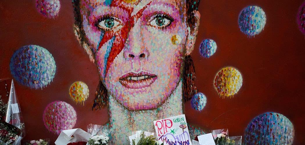 Tributes lie beneath a mural of British singer David Bowie by artist Jimmy C in Brixton, south London on Jan. 12, 2016. (Matt Dunham/AP)
