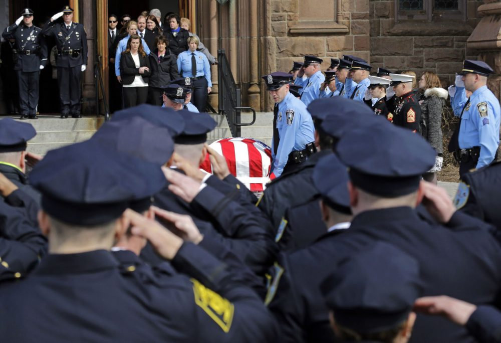 Police salute the casket of Prince William County, Va., Police Officer Ashley Guindon, as pallbearers exit Sacred Heart Church, Monday, in Springfield, Mass. Guindon, 28, a Springfield native, was killed during her first shift on the job Feb. 27 while responding to a domestic dispute in Woodbridge, Va. (Elise Amendola/AP)