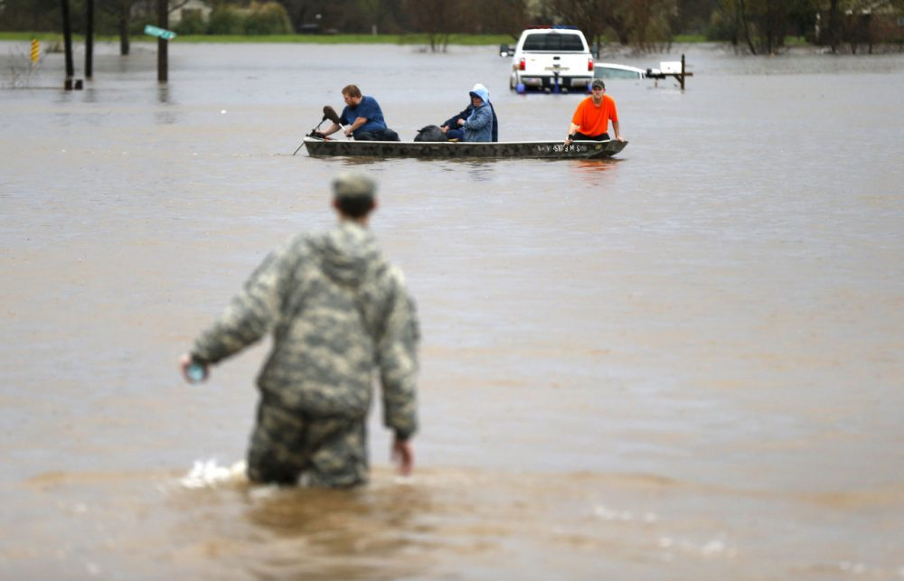 A Louisiana National Guardsman wades through water as residents are evacuated by boat through rising floodwaters in Bossier Parish, La., Thursday, March 10, 2016. (AP Photo/Gerald Herbert)
