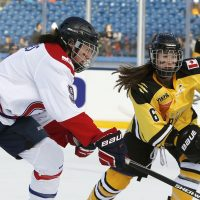 Montreal Les Canadiennes' Kim Deschenes (9) battles Boston Pride's Shannon Doyle for the puck during a women's outdoor hockey game at Gillette Stadium in Foxborough, Mass., Thursday, Dec. 31, 2015, where the Boston Bruins will play the Montreal Canadiens in the NHL Winter Classic on Friday. (AP Photo/Michael Dwyer)