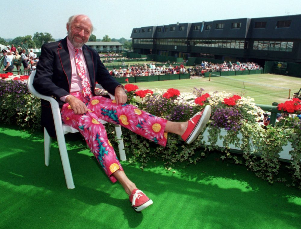 Sports journalist Bud Collins displays a pair of brightly-colored trousers as he sits overlooking the outside courts at Wimbledon in 1993. One of the country's foremost authorities on professional tennis, Collins died Friday at his home in Brookline. He was 86. (Gill Allen/AP)