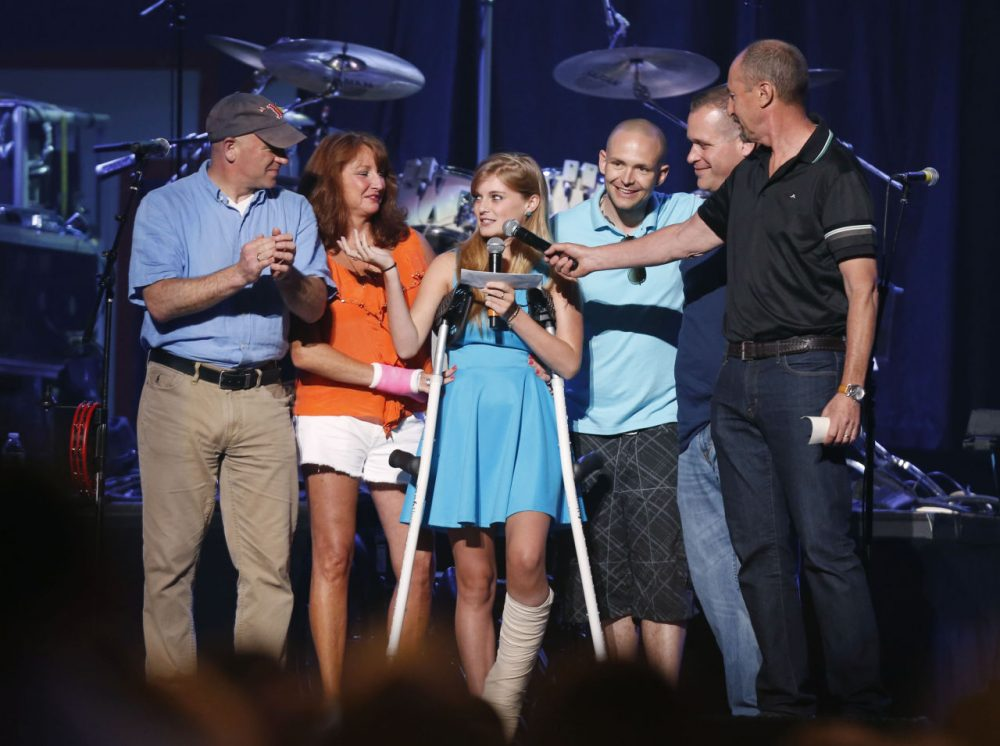 "Boston Marathon bombing survivor Victoria McGrath, center, thanks people who helped her when she was injured and helped her recovery during the ""Boston Strong Concert"" on May 30, 2013. (Bizuayehu Tesfaye/Invision/AP)"