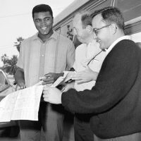 Boston Globe sports writer, Bud Collins (center) and Edwin Pope, assistant sports editor of the Miami Herald (right) insist on checking a road map at the start of the trek to Boston of the Muhammad Ali (Cassius Clay) entourage in Miami , Florida on April 30, 1965. Clay said he just drives from big town to big town, never mind the map. (AP Photo)