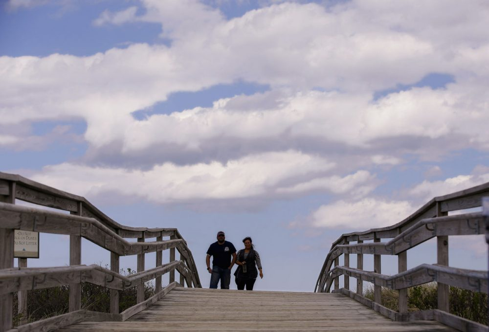 Two people walk across a beach bridge on Duxbury Beach. Duxbury is the first town on the south shore to institute a fine for underage drinking. (AP Photo/Stephan Savoia)