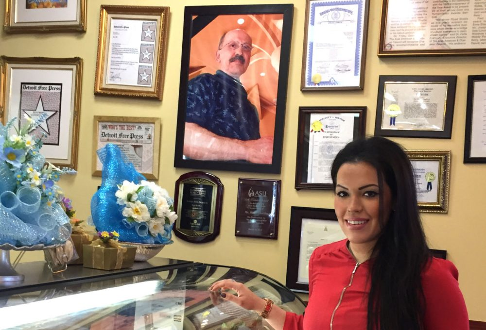 Nada Shatila, owner of Shatila Bakery & Cafe in Dearborn, Michigan, stands next to a photo of her father Riad Shatila, a Lebanese immigrant, founded it it 1979. (Robin Young/Here & Now)