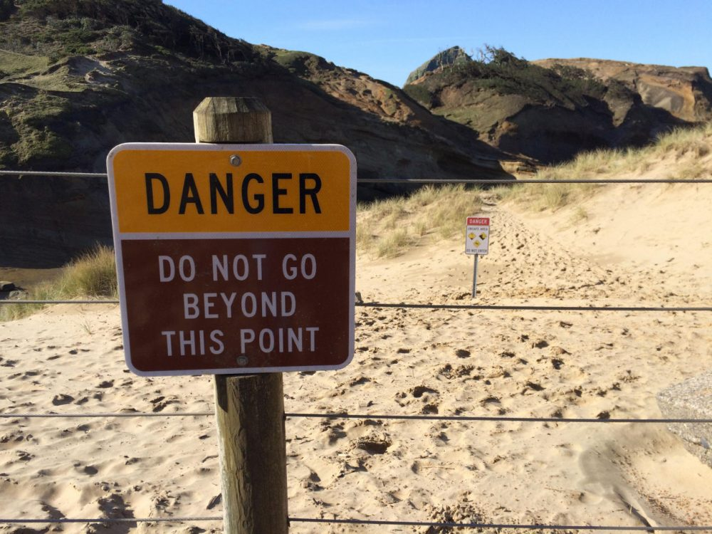 Footprints in the sand behind this fence show how frequently visitors ignore the warning signs at Cape Kiwanda. CHRIS LEHMAN / NORTHWEST NEWS NETWORK