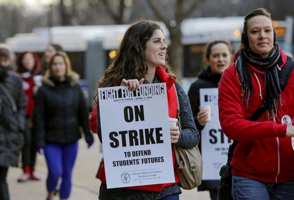 Colleen McDonough, a first-grade teacher at Walt Disney Magnet School in Chicago holds a picket sign outside the school, Friday, April 1, 2016,  during a one-day strike by Chicago teachers and supporters aimed at halting education funding cuts. (Teresa Crawford/AP)