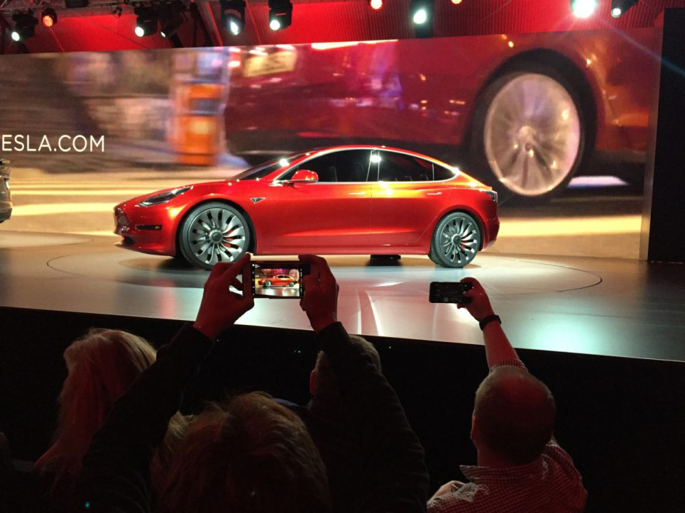 Tesla Motors unveils the new lower-priced Model 3 sedan at the Tesla Motors design studio Thursday, March 31, 2016, in Hawthorne, Calif. It doesn't go on sale until late 2017, but in the first 24 hours that order banks were open, Tesla said it had more than 115,000 reservations. Long lines at Tesla stores, reminiscent of the crowds at Apple stores for early models of the iPhone, were reported from Hong Kong to Austin, Texas, to Washington, D.C. Buyers put down a $1,000 deposit to reserve the car.  (AP Photo/Justin Prichard)