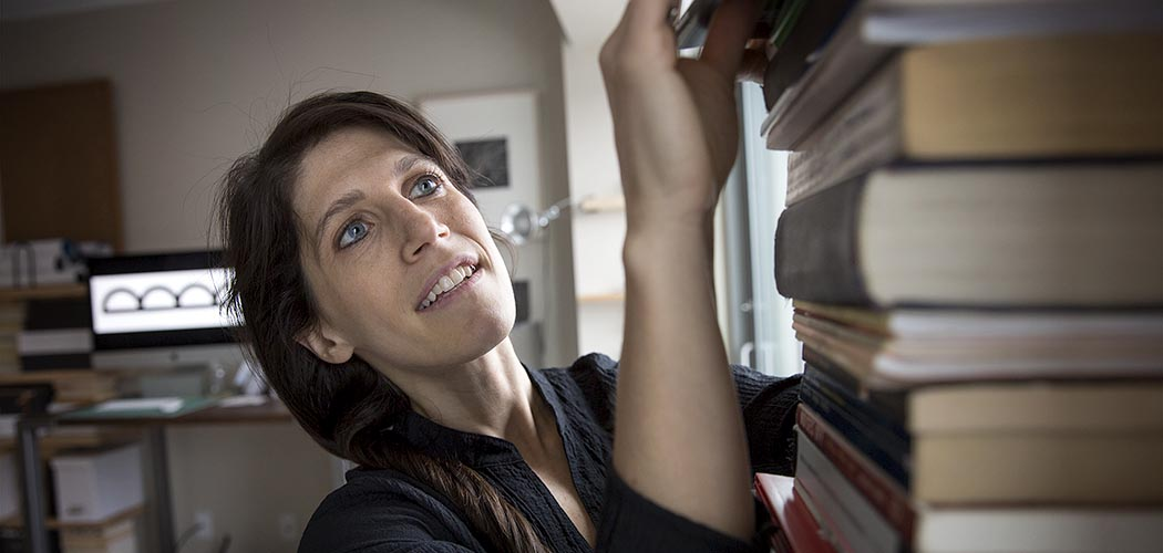 Olivia D'Ambrosio, producing artistic director of Bridge Repertory Theater, reaches for a play among a pile of books in her home office. (Robin Lubbock/WBUR)