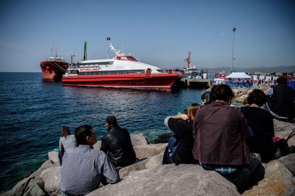 People gather on the beach as migrants deported from Greece arrive aboard a small Turkish ferry as part of an EU deal. (Ozan Kose/AFP/Getty Images)
