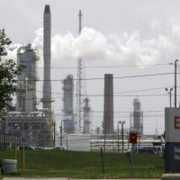 Did the oil giant lie to shareholders about business risks stemming from climate change? And how far did the corporation's efforts to sway scientific opinion go? In this 2010 photo, steam rises from towers at an Exxon Mobil refinery in Baytown, Texas. (Pat Sullivan/AP)