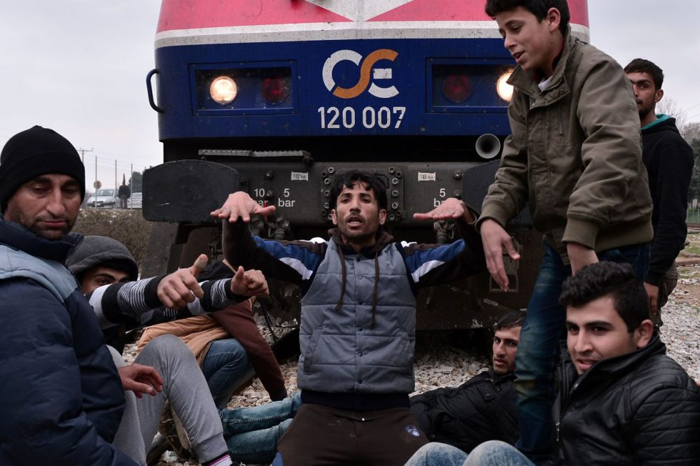 Syrian and Iraqi refugees trapped at the Greek-Macedonian borders stop an arriving train during their protest demanding the opening of the borders on February 28 , 2016.  A number of Balkan countries have closed their borders to migrants. (Louisa Gouliamaki/AFP/Getty Images)