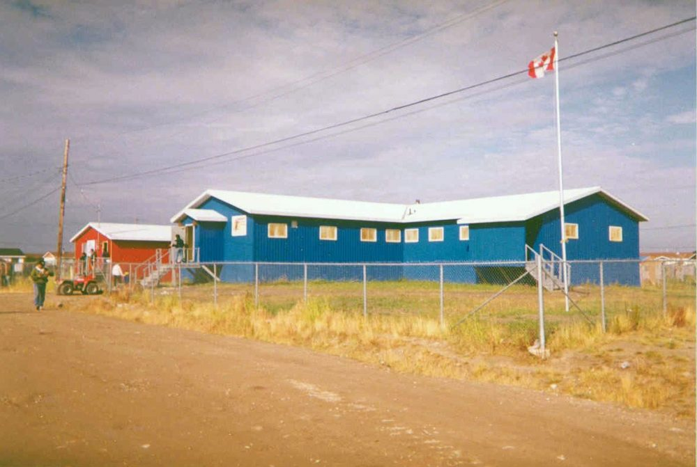 Office of the Attawapiskat First Nation in Attawapiskat, Ontario. The red building at left is post office. This photograph was taken in the early 1990s. (Paul Lantz/Wikimedia Commons)