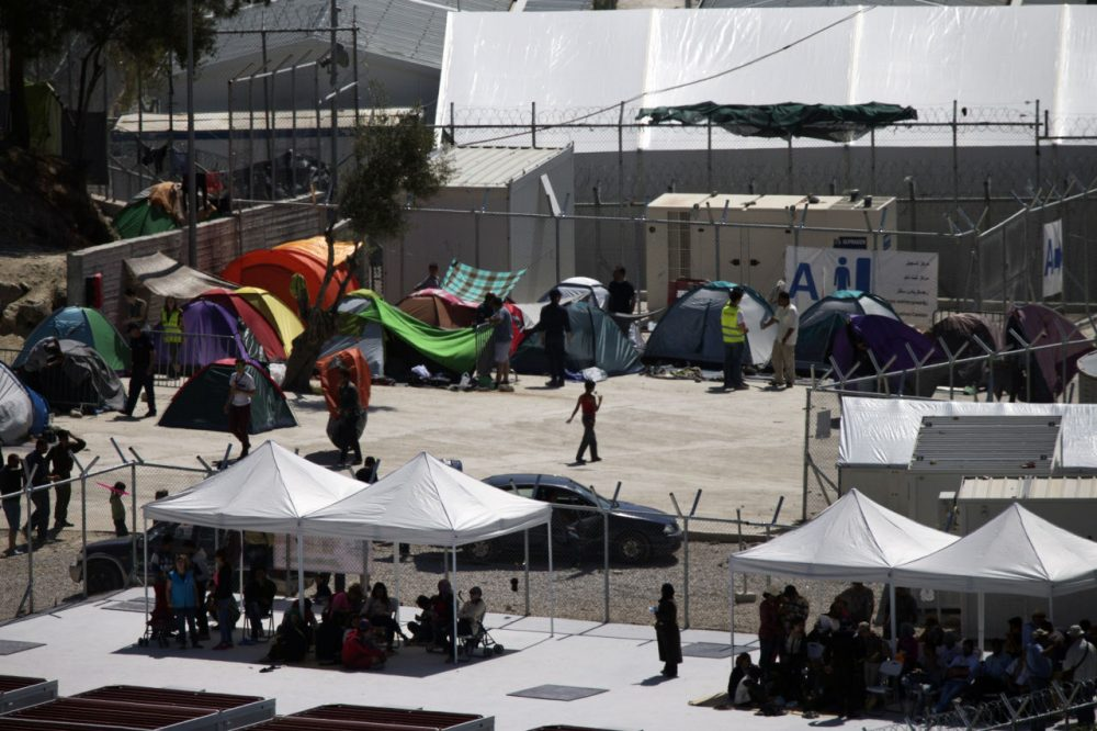 People sit under newly erected tents inside Moria camp on Lesbos island, Greece, where 2,300 migrants and refugees are being detained for deportation back to Turkey on Friday, April 15, 2016. Pope Francis will visit Moria camp Saturday, a mission human rights groups hope will highlight the plight of refugees who fled their war-ravaged homes only to be denied entry to Europe. Pope Francis will be joined by Ecumenical Patriarch Bartholomew and the head of the Orthodox Church of Greece, Athens Archbishop Ieronymos II. (Petros Giannakouris/AP)