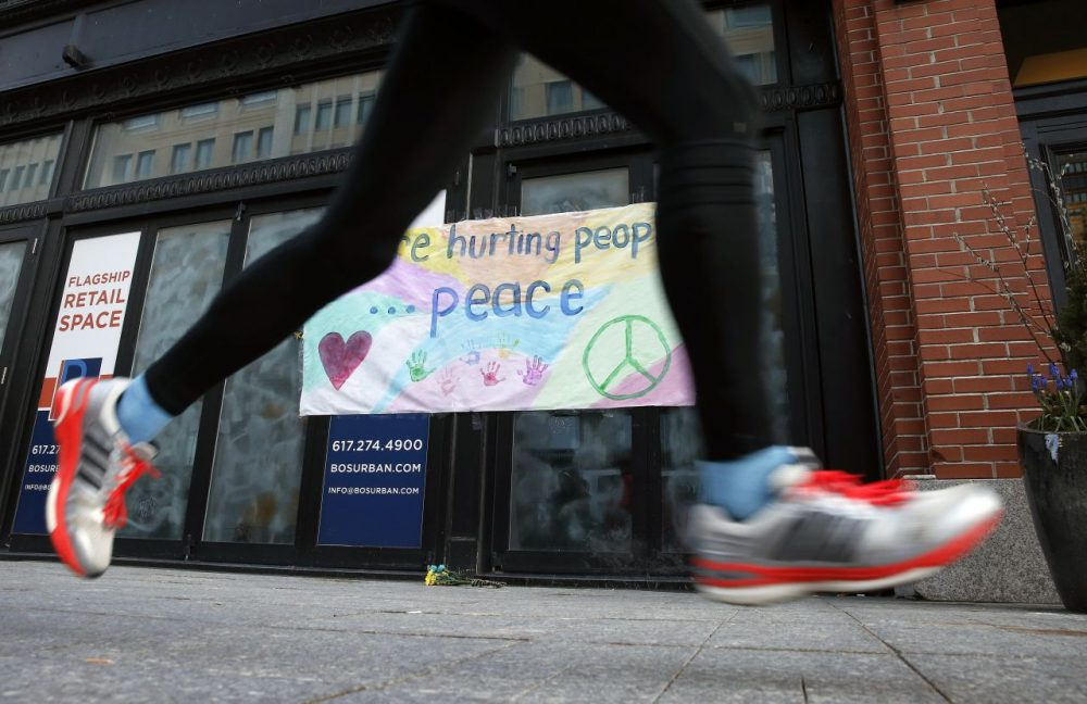 A runner passes the site of the second detonation on the third anniversary of the Boston Marathon bombings Friday. (Michael Dwyer/AP)