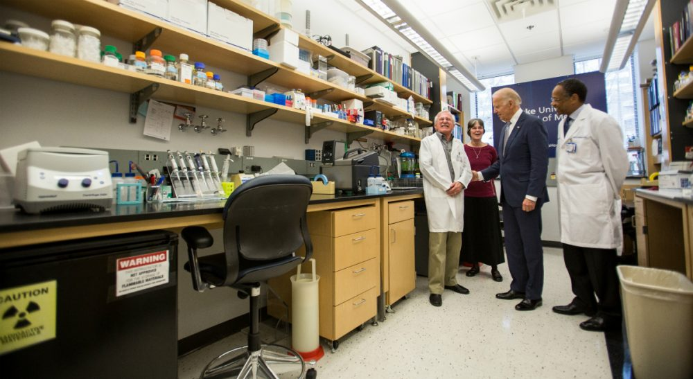 Vice President Joe Biden speaks with Nobel Laureate Dr. Paul Modrich, left, as Dr. A. Eugene Washington, Chancellor for Health Affairs at Duke University, right, and Vickers Burdett, wife of Dr. Modrich, middle listen in a laboratory at Duke University School of Medicine in Durham, N.C. Wednesday, Feb. 10, 2016. Vice President Joe Biden visited Duke to speak about his Cancer Moonshot initiative. (Ben McKeown/AP)