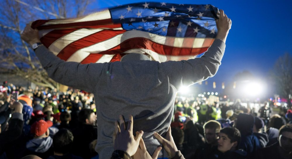 A Donald Trump supporter is hoisted up holding an American flag as the group faced off with Trump protesters, near the site of a campaign appearance by the Republican presidential candidate in Bethpage, N.Y., Wednesday, April 6, 2016. (Craig Ruttle/AP)