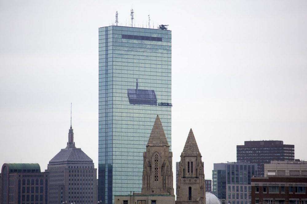 A crew lowers scaffolding ahead on the former John Hancock Building before removing JR's mural. (Jesse Costa/WBUR)