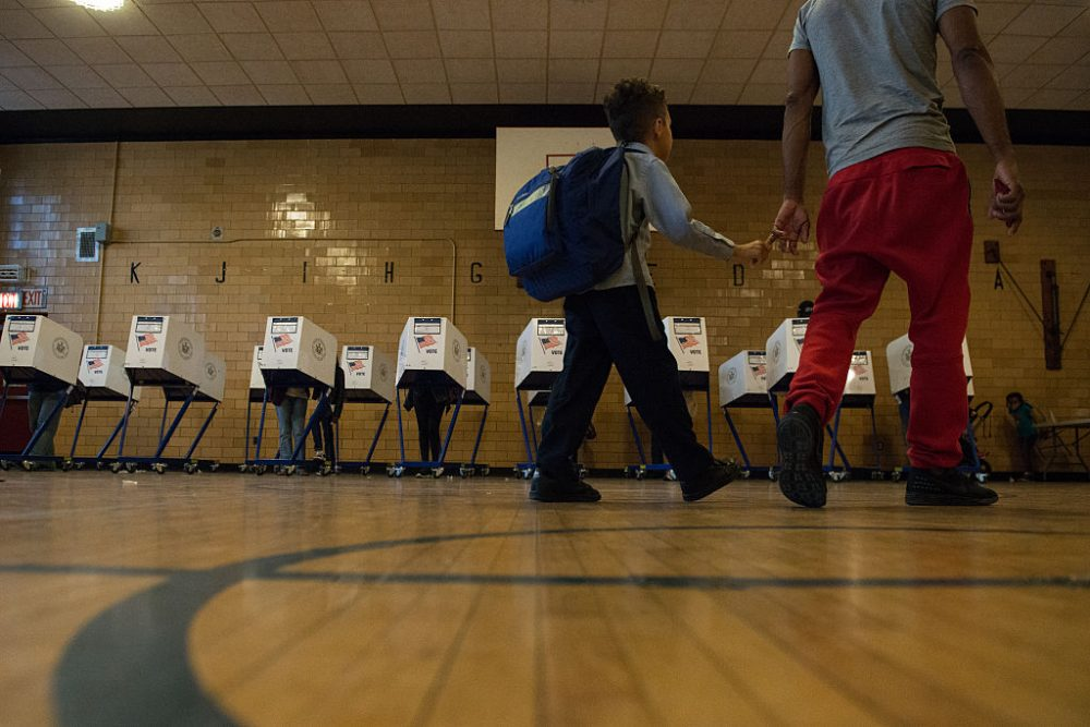 A man with his son walk past voting booths at Public School 22 on April 19, 2016 in the Brooklyn borough of New York City. Voters are going to the polls in New York for the presidential primary election. (Stephanie Keith/Getty Images)