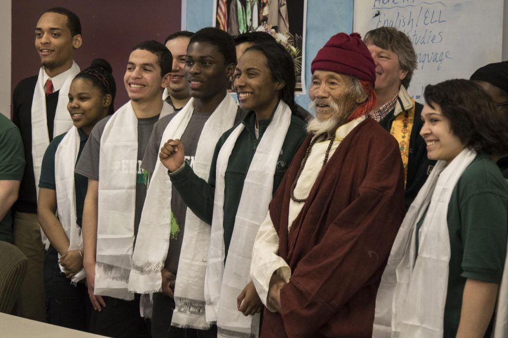 Thinley, an elder from the Nepalese village of Saldang, stands with students from Hartford's Academy of Engineering and Green Technology during his visit to the school Friday. (JACKSON MITCHELL/WNPR)