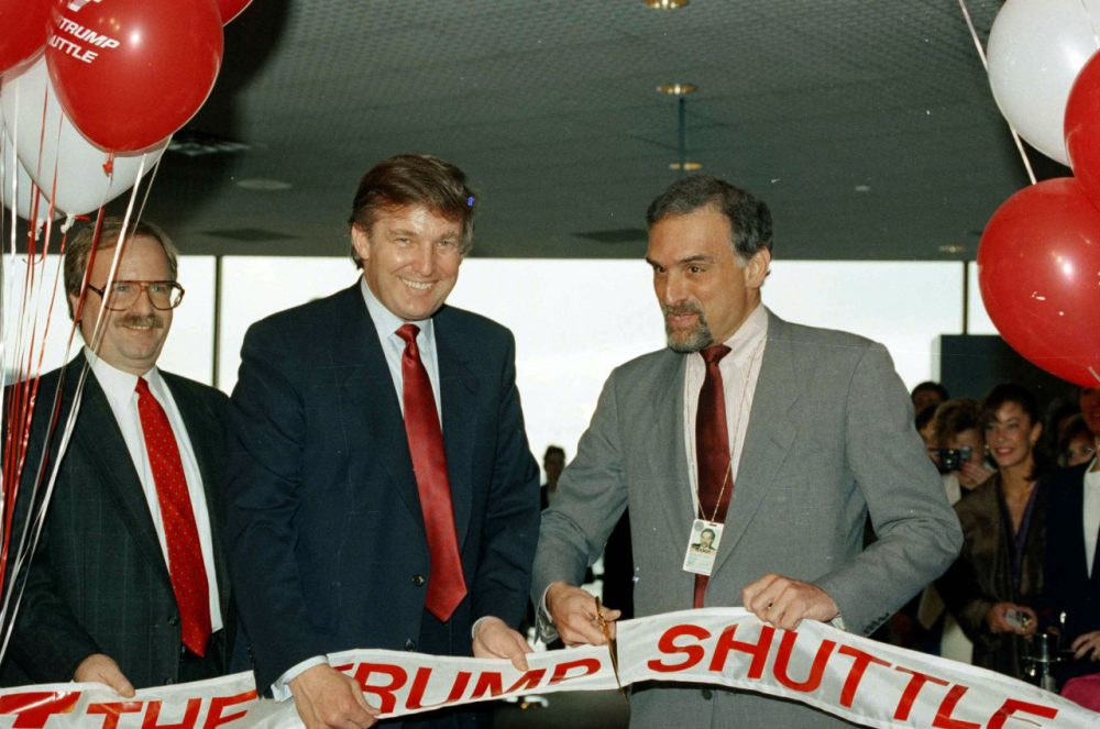 Donald Trump, second from left, holds a ribbon at Logan International Airport in Boston, as Massport deputy-executive director Patrick Moscaritolo cuts it to officially open the Trump Shuttle airline terminal on June 8, 1989. (Elise Amendola/AP)
