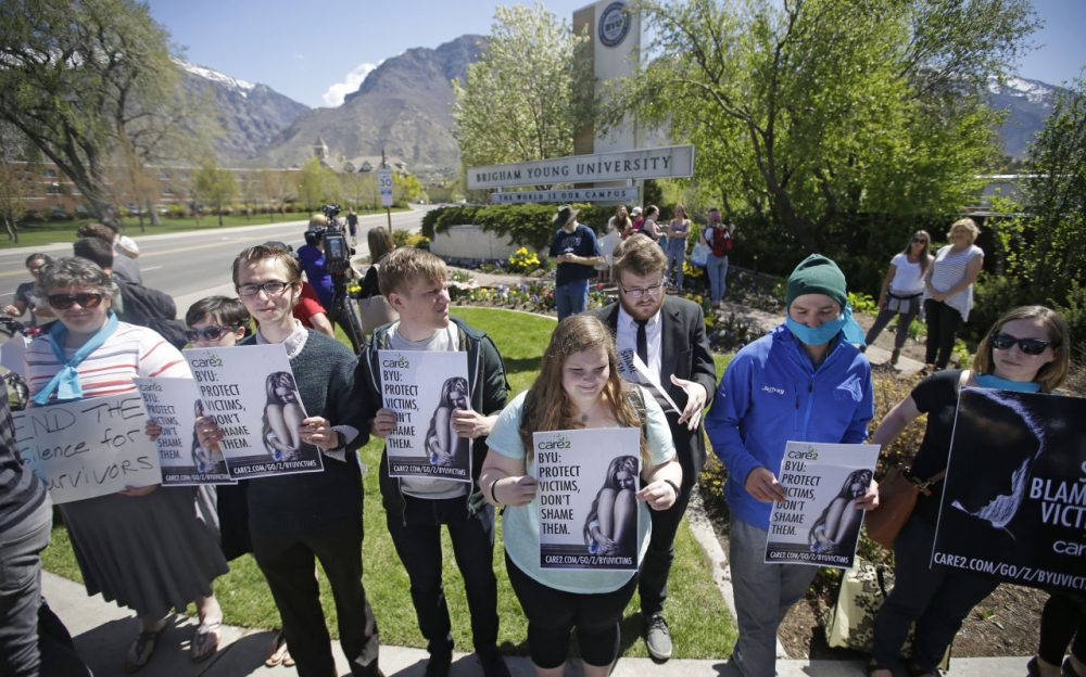 Protesters stand in solidarity with rape victims on the campus of Brigham Young University during a sexual assault awareness demonstration Wednesday, April 20, 2016, in Provo, Utah. BYU students who say they were sexually assaulted are finding themselves under investigation for possible violations of the Mormon school's honor code against sex and drinking. BYU says it will re-evaluate the practice. (Rick Bowmer/AP)