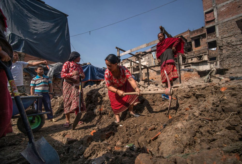 Bidhya Laxmi Prajapati, 45, works with a pickaxe as she clears debris at her former house  damaged during the April 2015 earthquake, together with family and neighbors on April 24, 2016 in Kathmandu, Nepal. Bidhya recently started rebuilding her house which collapsed during last year's earthquake after deciding not to wait any further for compensation promised by the government.  A 7.8-magnitude earthquake struck Nepal close to midday on April 25 lasts year. It was Nepal's worse earthquake in history as an estimated 9,000 people died and countless towns and villages across central Nepal were destroyed. Based on reports, the government promised 2,000USD to affected households but has only paid out a fraction of the amount so far and an estimated 660,000 families are still living in sub-standard temporary shelters or unsafe accommodation one year later.  (Tom Van Cakenberghe/Getty Images)