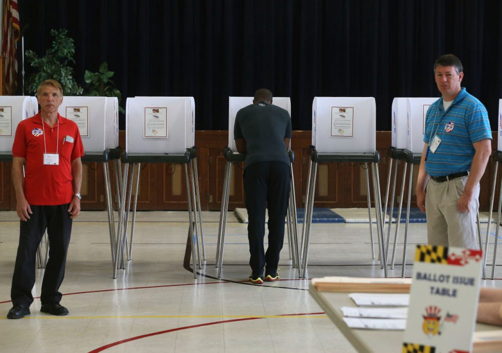 A man votes as volunteers stand nearby at the Mechanicsville Elementary School polling station, April 26, 2016 in Mechanicsville, Maryland. Maryland is one of five states that is holding their primary elections today. (Mark Wilson/Getty Images)