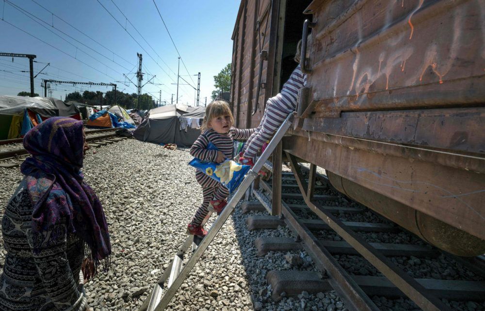 A woman watches over her daughters as they go up a ladder into a cargo train at a makeshift camp for migrants and refugees at the Greek-Macedonian border near the village of Idomeni on April 27, 2016. Some 54,000 people, many of them fleeing the war in Syria, have been stranded on Greek territory since the closure of the migrant route through the Balkans in February. (Joe Klamar/AFP/Getty Images)