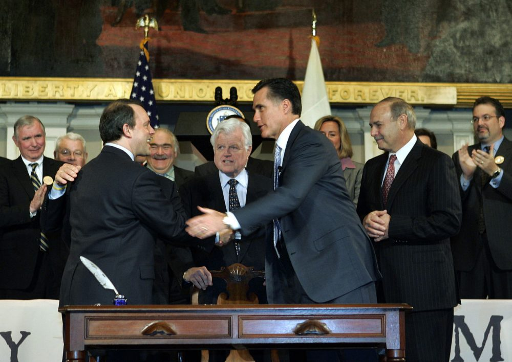 Then-Gov. Mitt Romney shakes hands with other political leaders at Faneuil Hall in Boston after signing into law the state's landmark health reform bill on April 12, 2006. (Elise Amendola/AP)