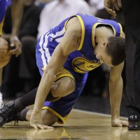 Golden State Warriors' Stephen Curry goes down with an injury during the first quarter of an NBA basketball game against the San Antonio Spurs, Wednesday, Dec. 8, 2010, in San Antonio. (AP Photo/Eric Gay)