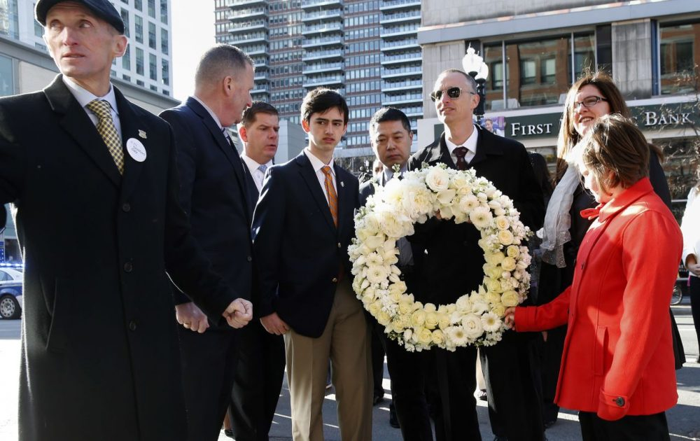 Members of the Richards family, along with the father of victim Lingzi Lu, Jun Lu, fourth from right, Boston Police Commissioner William Evans, left, and Mayor Marty Walsh prepare to place a wreath on the third anniversary of the bombings on Friday in Boston. (Michael Dwyer/AP)