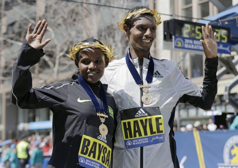 Atsede Baysa, left, and Lemi Berhanu Hayle, both of Ethiopia, pose for photos after winning the women's and men's races of the Boston Marathon on Monday. (Elise Amendola/AP)