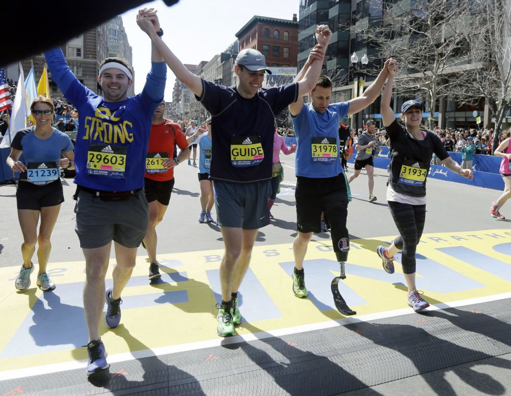 Boston Marathon bombing survivor and amputee Patrick Downes, second from left, crosses the finish line with companions Monday. (Elise Amendola/AP)