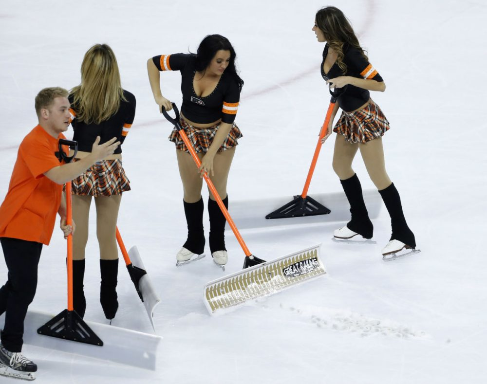 Ice crew personnel had to clean up promotional bracelets that were thrown onto the ice during the third period of Game 3 between the Philadelphia Flyers and the Washington Capitals in the first round of the NHL Stanley Cup hockey playoffs, Monday, April 18, 2016, in Philadelphia. Washington won 6-1. (AP Photo/Matt Slocum)