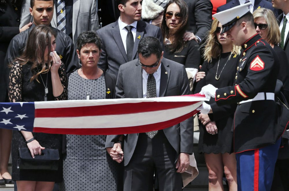 Linda Orlando, center, and her husband Richard Orlando pause as a flag is folded during a memorial ceremony for their son, U.S. Marine Cpl. Christopher Orlando, outside St. Paul's Church in Hingham Friday. (Charles Krupa/AP)