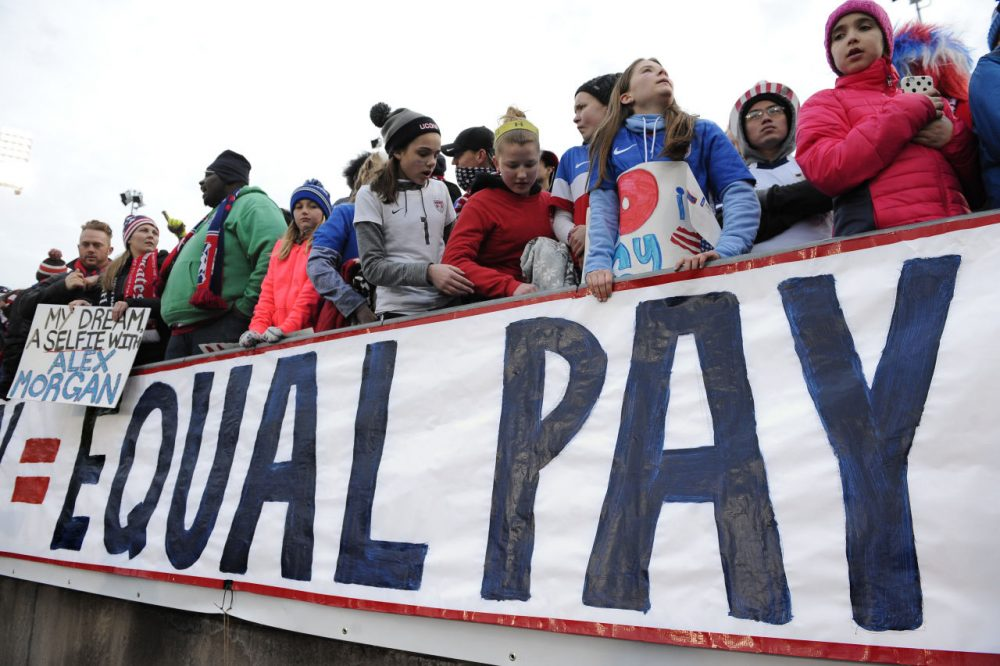 Fans stand behind a large sign for equal pay for the women's soccer team on April 6, 2016, in East Hartford, Conn. (AP Photo/Jessica Hill)