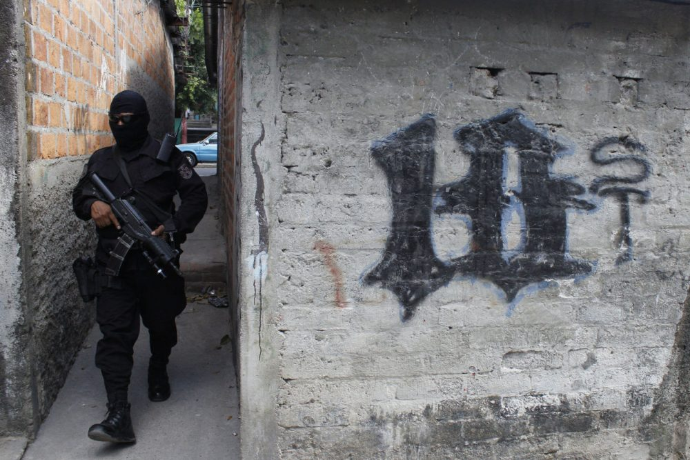 In this April 5, 2016 photo, a masked and armed policeman patrols a gang controlled neighborhood in San Salvador, El Salvador. Hyper-violent gangs declared open-season on police in this Central American nation in response to a government crackdown that began last year. Justice and Security Minister Mauricio Ramirez Landaverde, who was national police director until January, acknowledged that security forces are vulnerable. (AP Photo/Alex Peña)