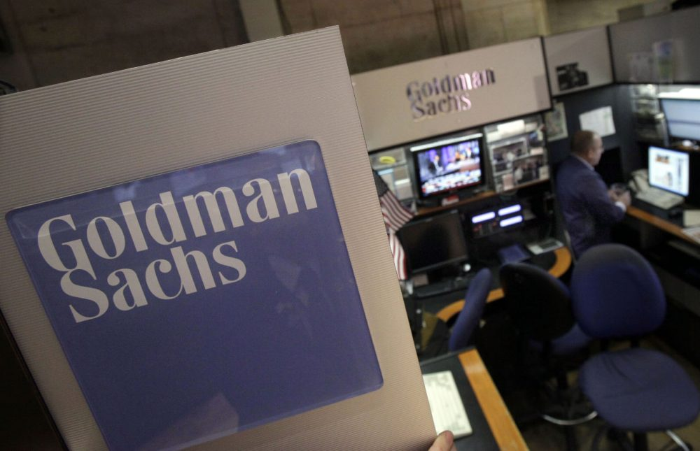 In this March 15, 2012 photo, a trader works in the Goldman Sachs booth on the floor of the New York Stock Exchange.  Goldman Sachs reached a $5 billion settlement as part of a federal and state probe into its role in the sale of mortgages in the years leading up into the housing bubble and subsequent financial crisis. (Richard Drew/AP)