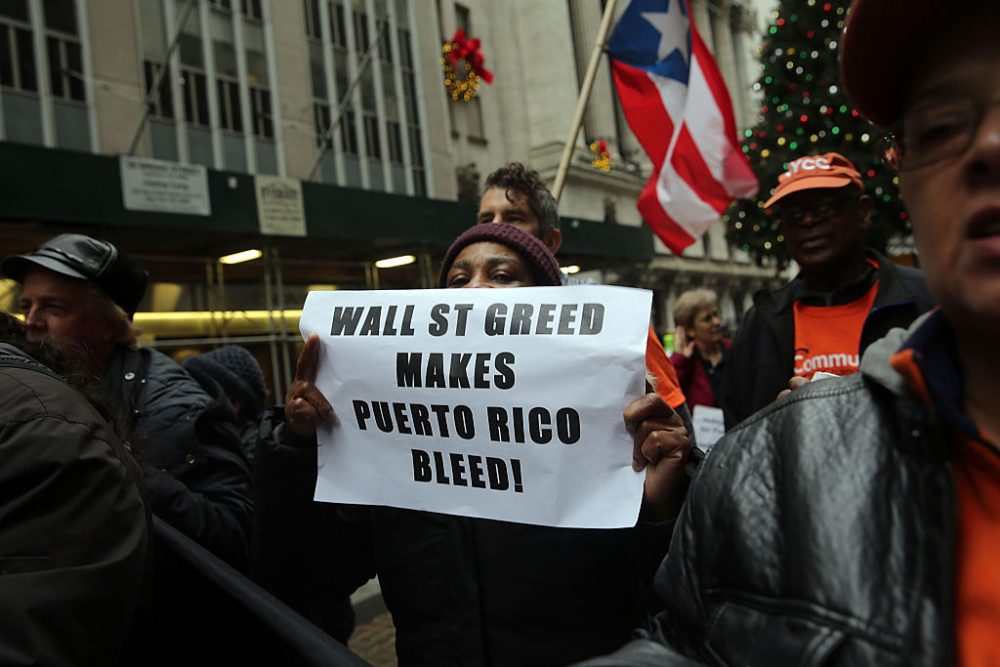 People protest outside of Wall Street against cutbacks and austerity measures forced onto the severely indebted island of Puerto Rico on December 2, 2015 in New York City. Puerto Rico made a $355 million payment on Tuesday on its bond debt to stave off a default. Officials have warned that the commonwealth's fiscal position remain dire. (Spencer Platt/Getty Images)