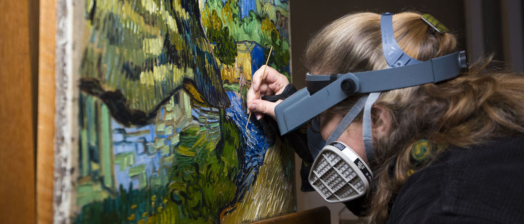 """MFA conservator Lydia Vagts works on removing the varnish from Vincent van Gogh's """"Houses at Auvers."""" (Jesse Costa/WBUR)"""
