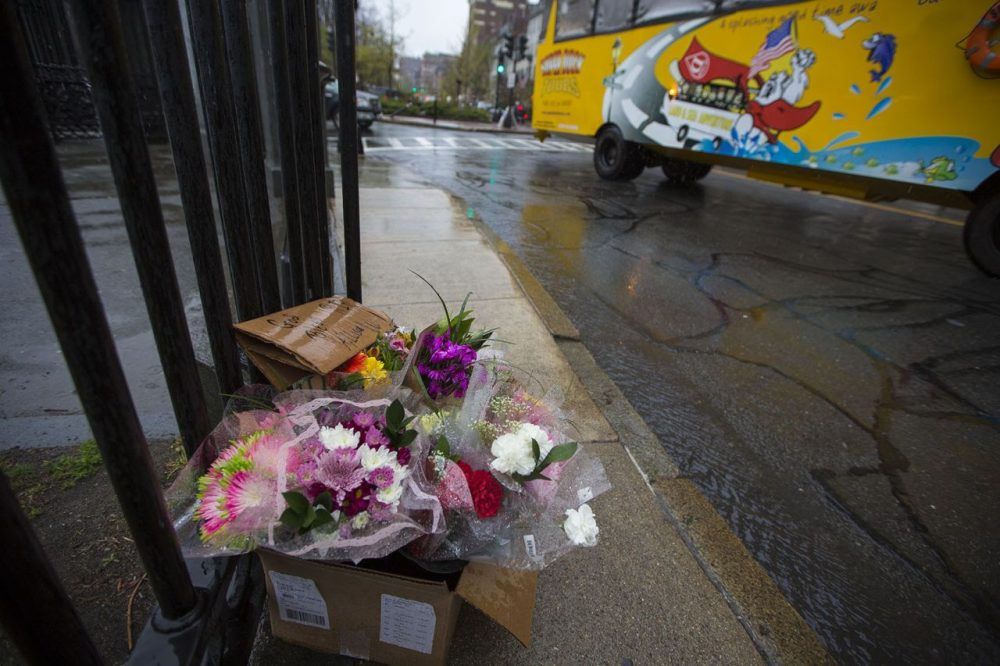 A duck boat tour bus passes by a memorial for Allison Warmuth in the rain on the corner of Charles and Beacon Streets. (Jesse Costa/WBUR)