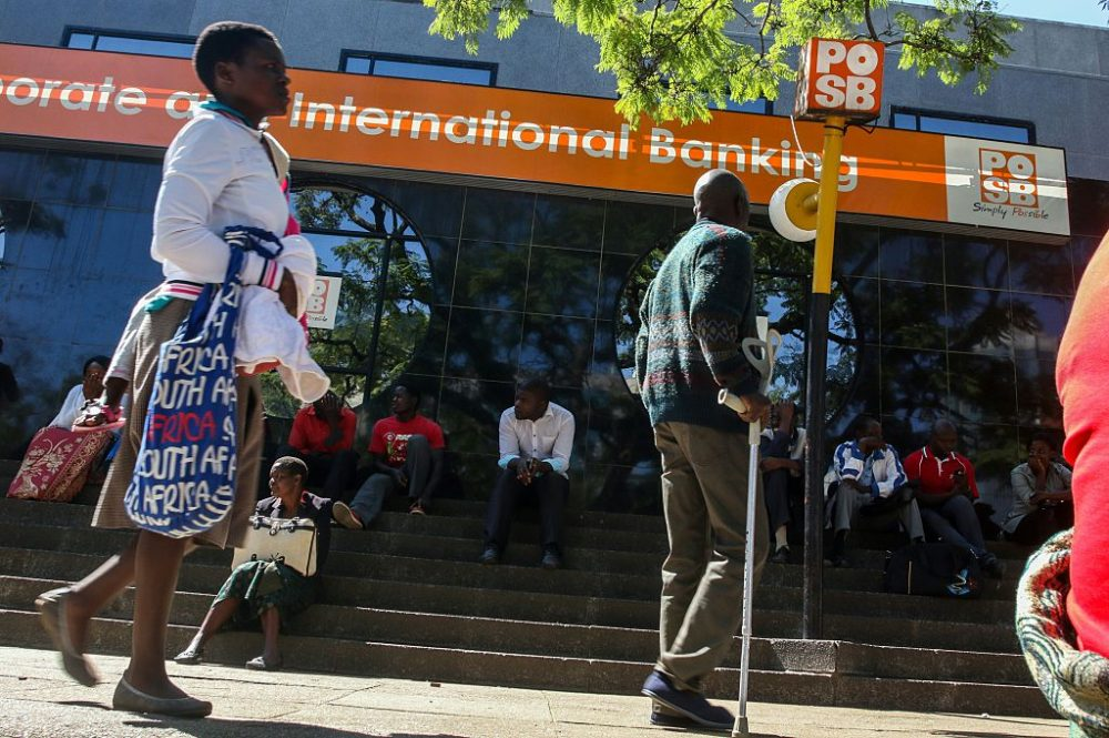 """Zimbabweans queue to withdraw cash outside a bank on May 5, 2016 in Harare, Zimbabwe.   Zimbabweans formed long queues outside banks Thursday after the government slapped new limits on cash withdrawals and announced that """"bond notes"""" at par with the US dollar would be introduced. (JEKESAI NJIKIZANA/AFP/Getty Images)"""