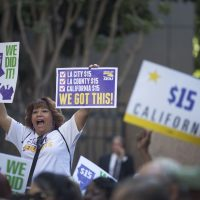 Service Employees International Union members celebrate after California Governor Jerry Brown signed landmark legislation SB 3 into law on April 4, 2016 in Los Angeles, California. The law makes California the first state in the nation to commit to raising the minimum wage to $15 per hour statewide. (David McNew/Getty Images)