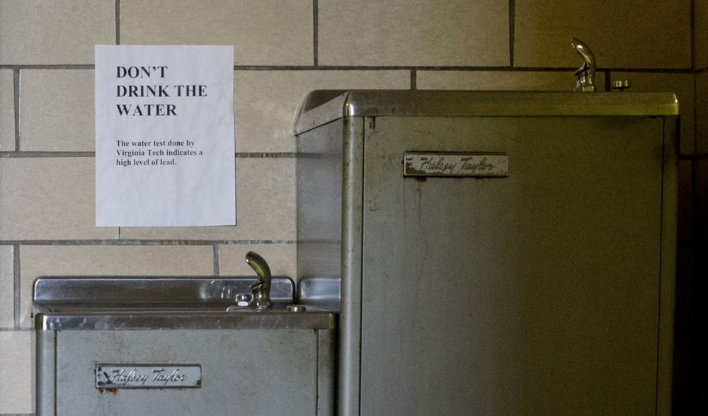 A sign warns people not to drink water contaminated with lead from a fountain in Flint, Mich. But Flint isn't the only place concerned about its water. Four schools in Boston believe a miscommunication may have led to students being exposed to lead-tainted water. (Jacquelyn Martin/AP)