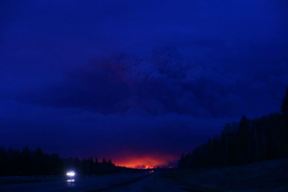 A plume of smoke hangs in the air as forest fires rage on in the distance in Fort McMurray, Alberta on May 4, 2016. Numerous vehicles can be seen abandoned on the highways leading from the raging forest fires in Fort McMurray and neighbouring communities have banded together to offer support in the form of food, water, and gasoline.  (Cole Burston/AFP/Getty Images)