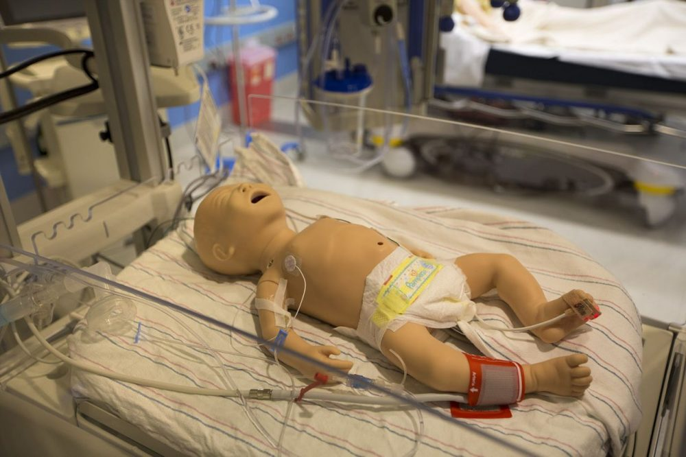A simulation doll of a very young child lying on a hospital bed in the ICU simulation room. (Jesse Costa/WBUR)